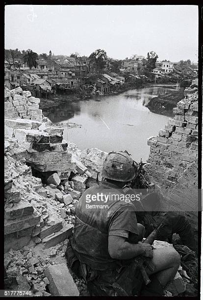 From an elevated position behind a shattered wall two US Marines scan a string of shacks along a canal in Hue as they look for enemy soldiers to make...