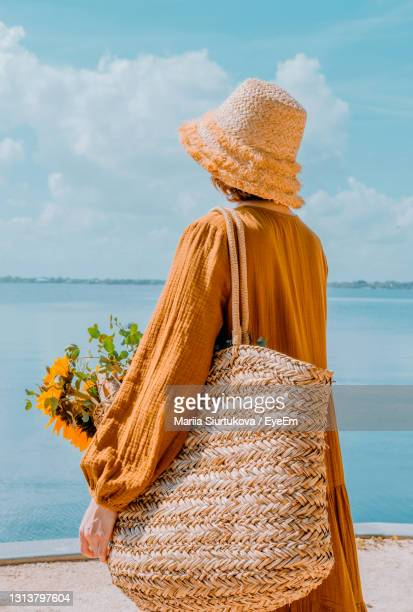 from behind woman resting on  beach. girl in straw hat enjoying the beautiful view. photos from back - straw hat stock pictures, royalty-free photos & images