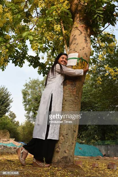 MLA from Chandni Chowk Alka Lamba hugs a tree during a protest against the cutting of trees at Sarojini Nagar on June 24 2018 in New Delhi India...