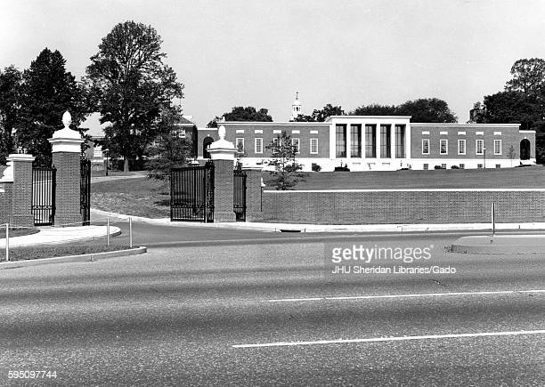 From Charles Street the entryway and Merrick Gateway leading into Johns Hopkins University with the grassy lawn known as the Beach and the Milton S...