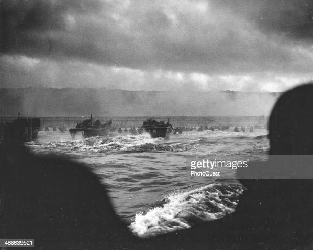 From Coast Guard landing barges hitting the French Coast with the first waves of invaders American fighting men wade ashore under heavy machinegun...