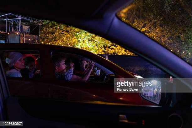 From inside their cars opera fans applaud the performance of Puccini's La bohème performed by members of English National Opera as a drivein at...