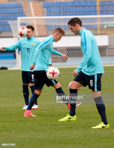 Australia's forward Jamie Maclaren midfielder Ajdin Hrustic and defender Dylan McGowan take part in a training session at the Petrovsky Stadium in...