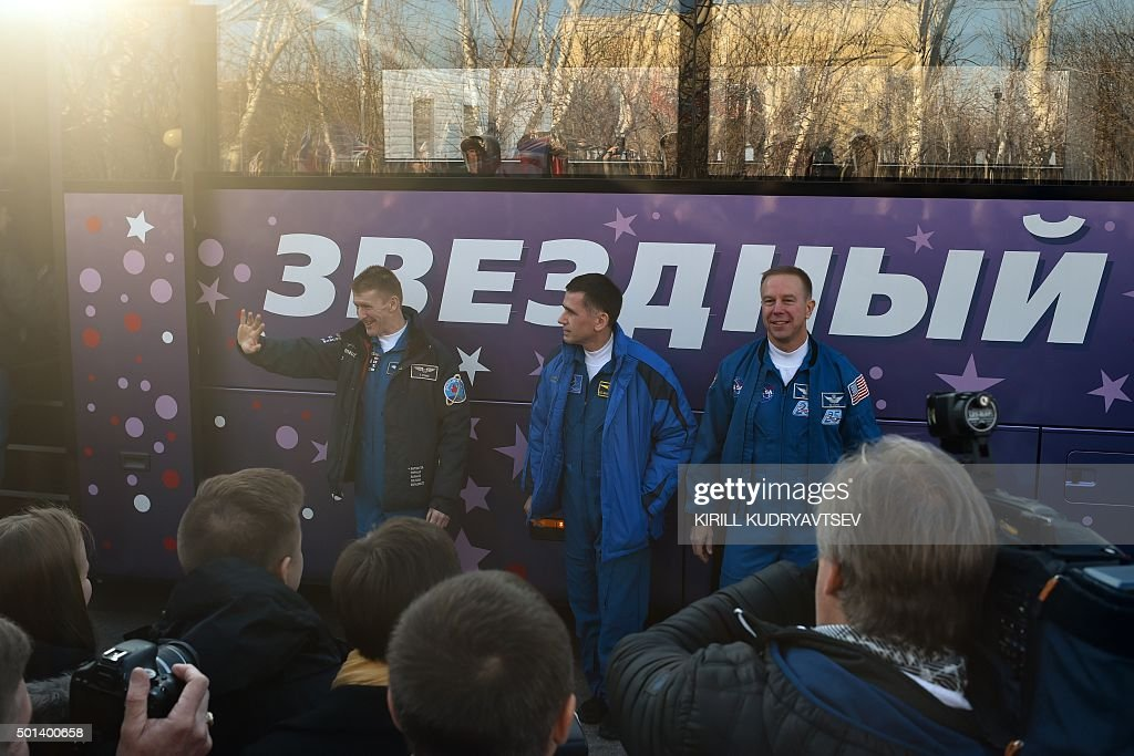 Britain's astronaut Tim Peake, Russian cosmonaut Yuri Malenchenko and US astronaut Tim Kopra pose for pictures near a bus during a sending-off ceremony at the Russian-leased Baikonur cosmodrome on December 15, 2015. Russia's Soyuz TMA-19M spacecraft carrying the International Space Station (ISS) Expedition 46/47 crew of Britain's astronaut Tim Peake, Russian cosmonaut Yuri Malenchenko and US astronaut Tim Kopra is scheduled to blast off to the ISS on December 15, 2015.