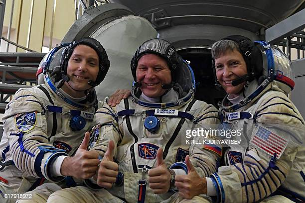 France's astronaut Thomas Pesquet Russia's cosmonaut Oleg Novitsky and US astronaut Peggy Whitson pose for pictures in front of a Soyuz space vehicle...