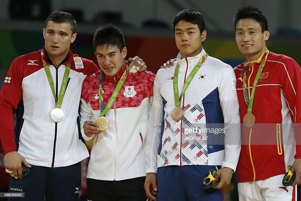 Georgia's Varlam Liparteliani (silver), Japan's Mashu Baker (gold), South Korea's Gwak Donghan (bronze) and China's Cheng Xunzhao (bronze) celebrate on the podium of the men's -90kg judo contest of the Rio 2016 Olympic Games in Rio de Janeiro on August 10, 2016. / AFP / Jack GUEZ