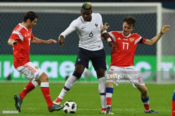 Russia's midfielder Alan Dzagoev France's midfielder Paul Pogba and Russia's midfielder Alexander Golovin vie for the ball during an international...