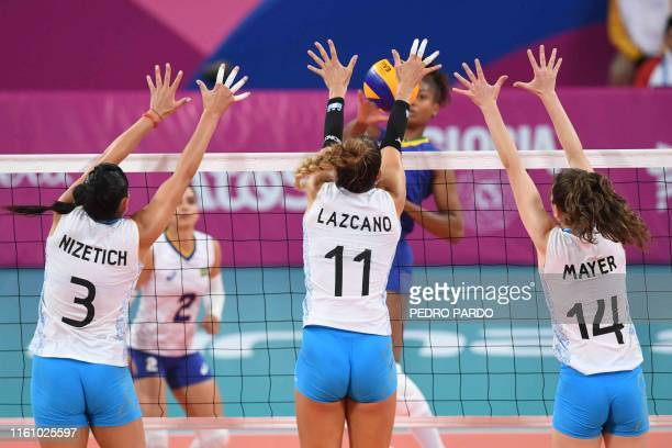 From L to R Argentina's Paula Nizetich Julieta Lazcano and Victoria Mayer jump to block a ball during the Women's Volleyball Bronze Medal in the Lima...