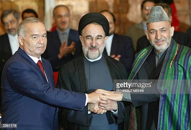 Uzbek President Islam Karimov Iranian President Mohammad Khatami and their Afghan counterpart Hamid Karzai put their hands together after signing an...