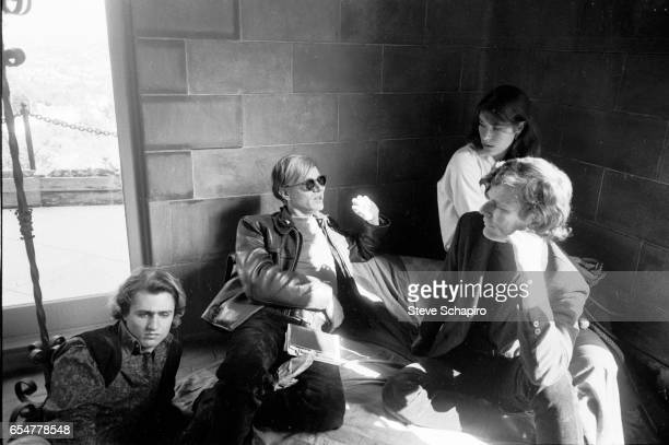 From left actor Gerard Malanga Pop artist Andy Warhol actress Mary Woronov and an unidentified man sit in a corner in a mansion nicknamed 'the...