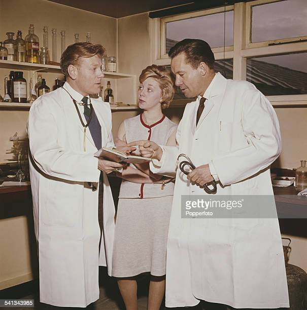 From left actors Desmond Carrington Jill Browne and Charles Tingwell pictured together filming a scene from the television soap opera Emergency Ward...