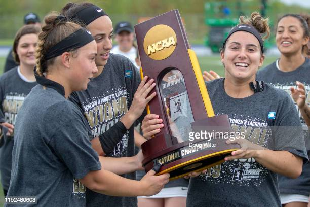 From left Alyssa Gillespie Chelsea Abreu and Nicki Stanco of the Adelphi Panthers hoist the national championship trophy during the 2019 Division II...