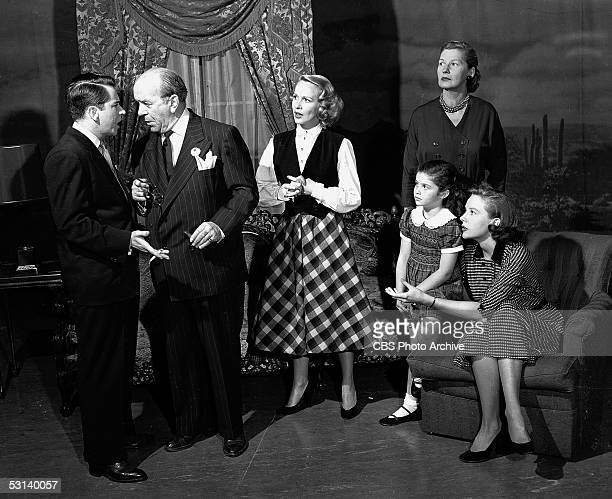 From left American actor John Sylvester talks with Cliff Hall as actresses Sara Anderson Lynn Loring Bess Johnson and Mary Stuart watch in a scene...