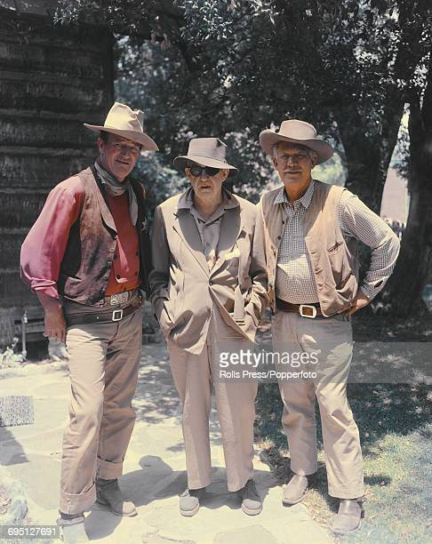 From left American actor John Wayne American film director John Ford and fellow American actor Ward Bond pictured together on the set of a Western...