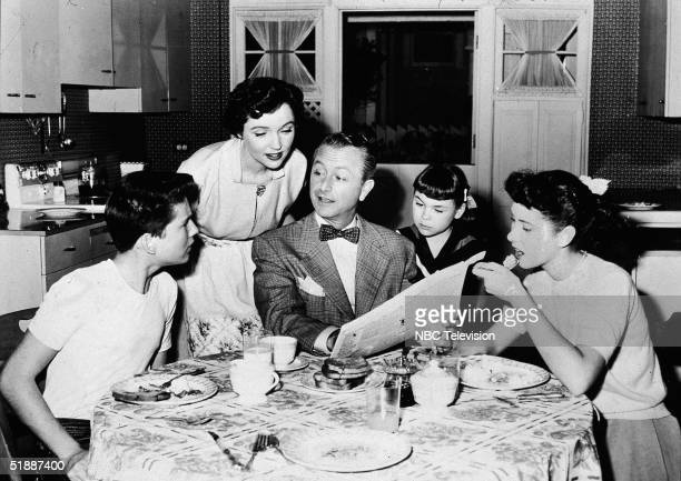 American actors Billy Gray Jane Wyatt Robert Young Lauren Chapin and Elinor Donahue look at a newspaper as they eat at the kitchen table on an...