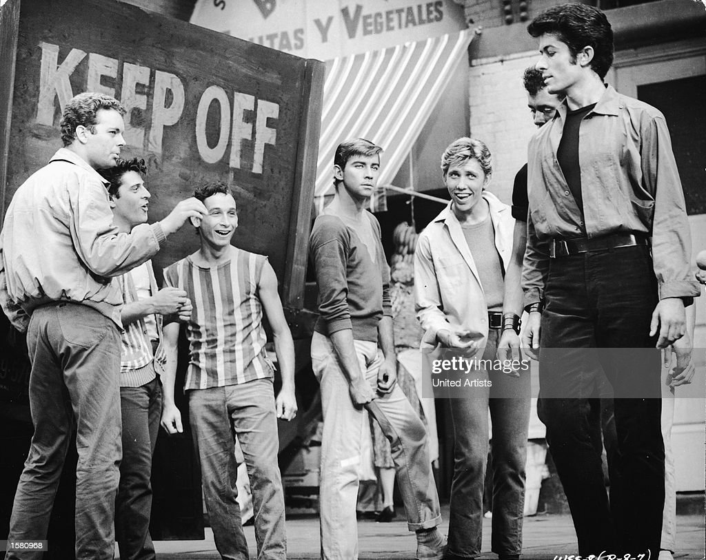 From left, American actors Russ Tamblyn, Tony Mordente, Bert Michaels, Tucker Smith (1936 - 1988), and Anthony 'Scooter' Teague (1940 - 1989) taunt George Chakiris in a still from the film, 'West Side Story,' directed by Jerome Robbins and Robert Wise, 1961.