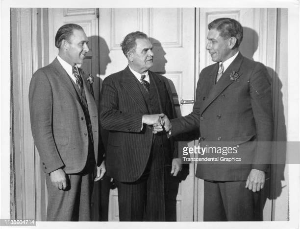 From left American baseball player Rube Walberg watches as Temple University football coach Pop Warner shakes hands with former baseball player Chief...