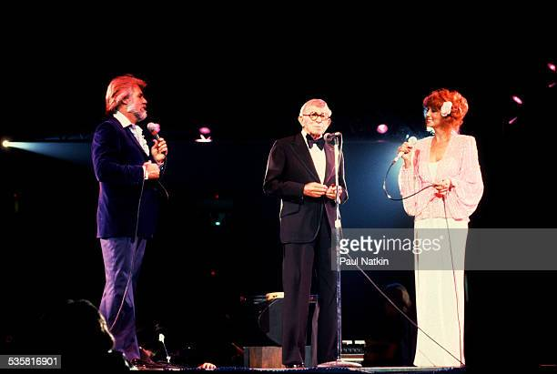 From left American musician Kenny Rogers comedian George Burns and singer Dottie West perform at the Rosemont Horizon Rosemont Illinois May 17 1980