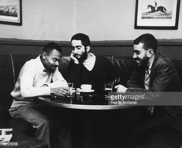 From left American poet and playwright LeRoi Jones editor and poet Irving Rosenthal and poet and musician Michael John Fles share a laugh over drinks...