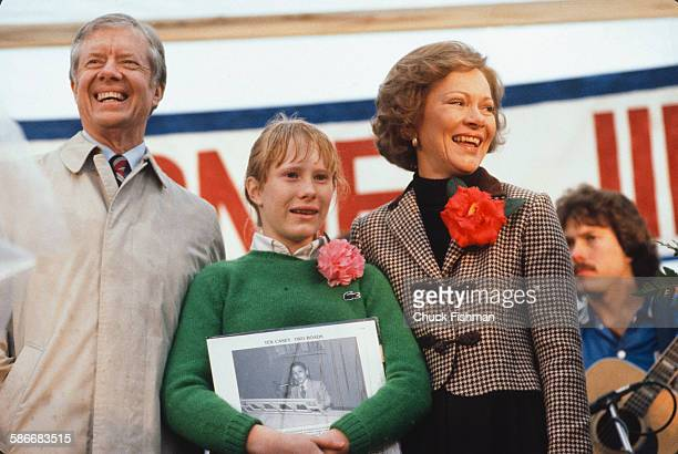 From left American politician and former US President Jimmy Carter his daughter Amy and wife Rosalynn smile as they stand on a podium upon the...