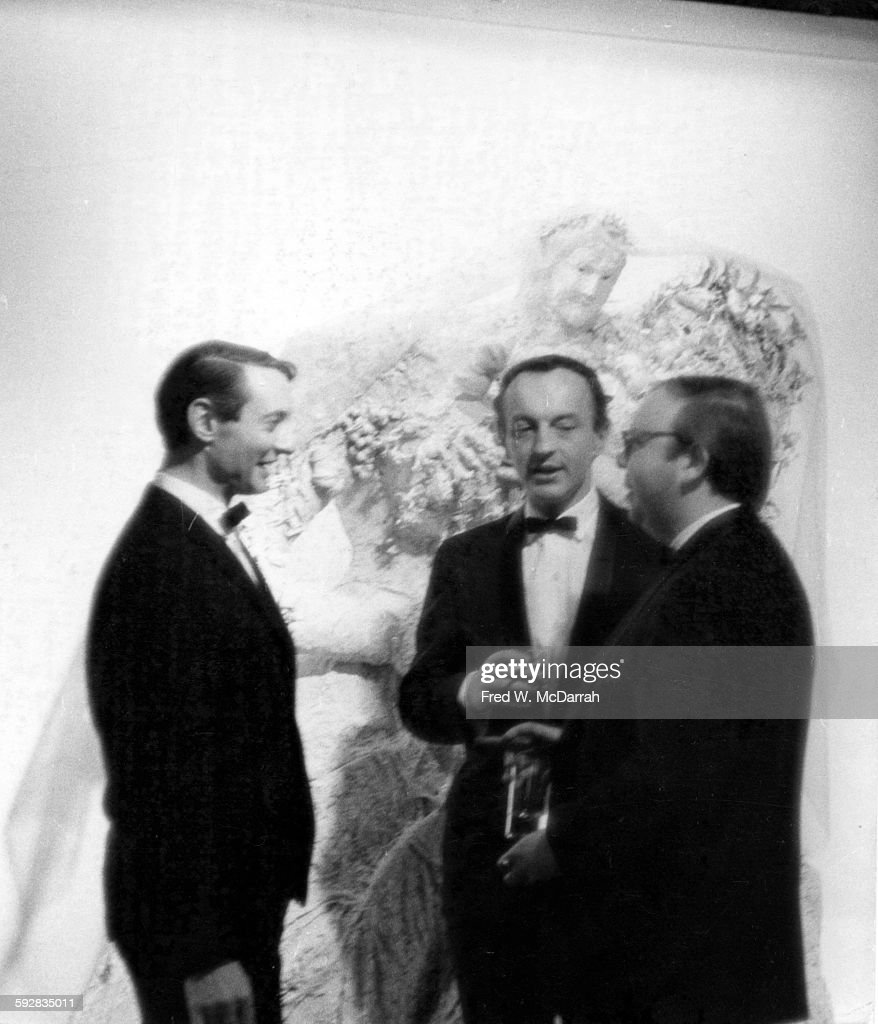 From left, American Pop artist Roy Lichtenstein (1923 - 1997), author and critic Frank O'Hara (1926 - 1966), and curator and critic Henry Geldzahler (1935 - 1994) talk together as they attend a Parke-Bernet auction, New York, New York, April 14, 1965.