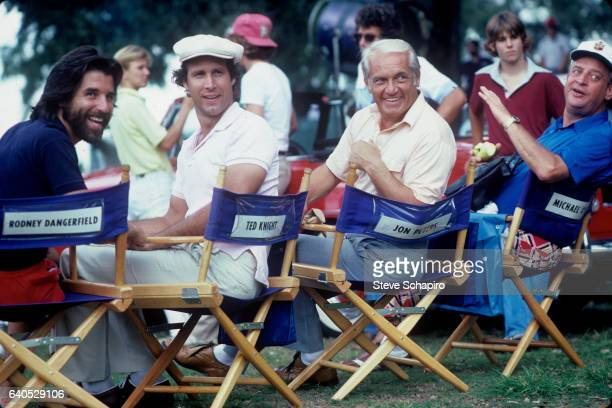 From left American producer Jon Peters and actors Chevy Chase Ted Knight and Rodney Dangerfield sit on another's chairs on the set of their film...