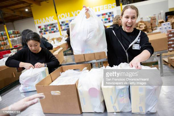 Amy Poon and Molly Matles tie food bags at the Alameda County Community Food Bank that will be distributed to furloughed government employees on...