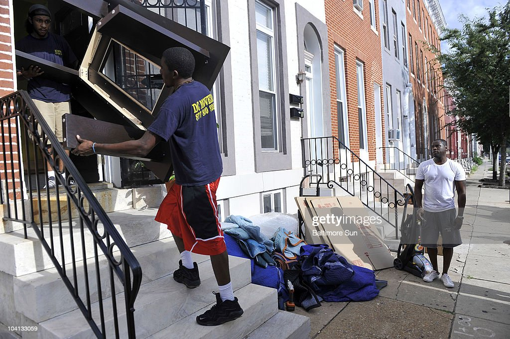 From Left, Andrew Oku And Mike Davis Of DC Movers Move Furniture As Wallace  Farmer Pictures