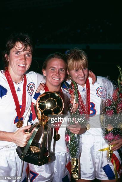From left, April Heinrichs, Tracey Bates and Shannon Higgins hold up the trophy in celebration after the United States team beat Norway 2-1 in the...