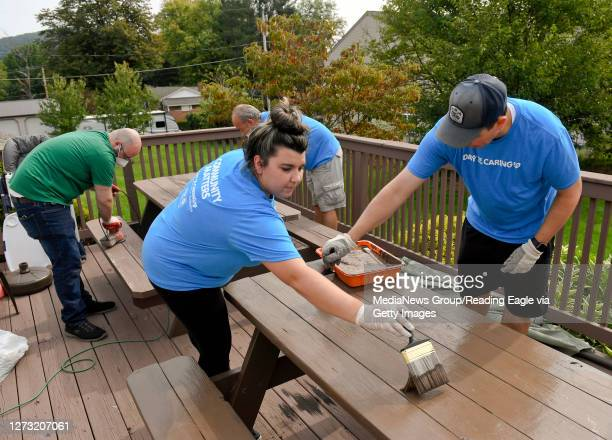 From left are Herbein employees Jacinda Ruzicka, senior account and Chris Kunkle, senior manager, staining a picnic table. At Hannah's Hope...