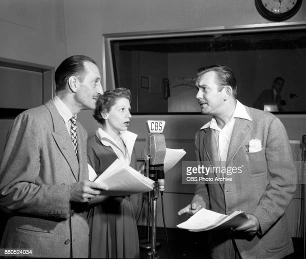 From left Basil Rathbone lead actor in the CBS Radio crime drama program Tales of Fatima with unidentified actor and Francis De Sales Image dated...