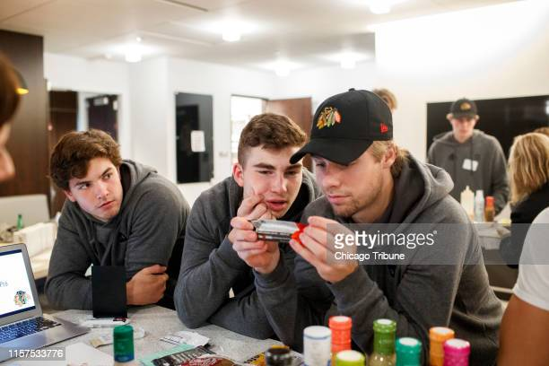 From left Blackhawks prospects Michal Teply Kirby Dach an Brandon Hagel read sports bar ingredients while attending a nutrition and cooking class in...