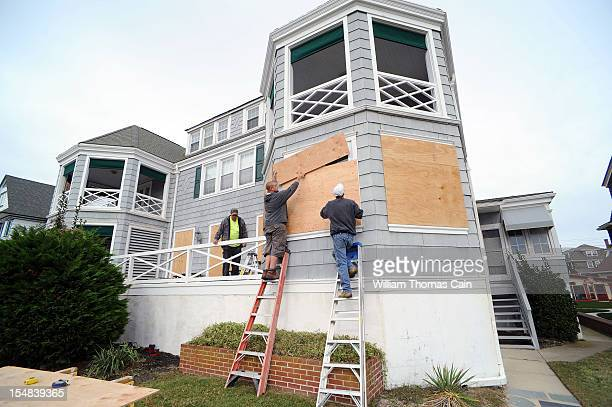 From left, Bob Grabenstetter, Paul Young and Mike Kern board up the Mae West Hotel in preparation for Hurricane Sandy October 27, 2012 in Cape May,...
