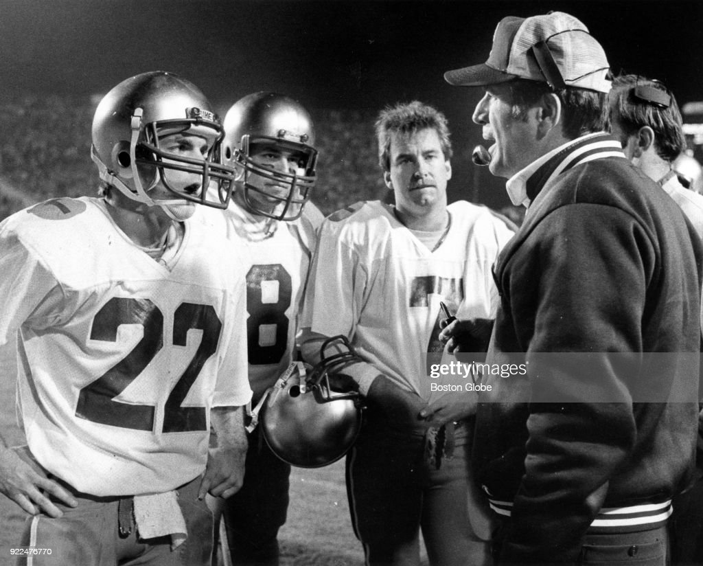 From left, Boston College Doug Flutie, Dennis Scala and John Loughery listen to coach Jack Bicknell during the Tangerine Bowl against Auburn University in Orlando, Fl., Dec. 18, 1982.