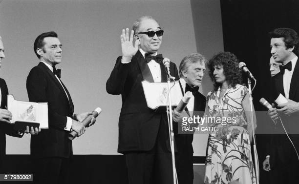 British actor Dirk Bogarde US actor and President of Cannes Film Festival's jury Kirk Douglas an unidentified woman and Michel Drucker surround...