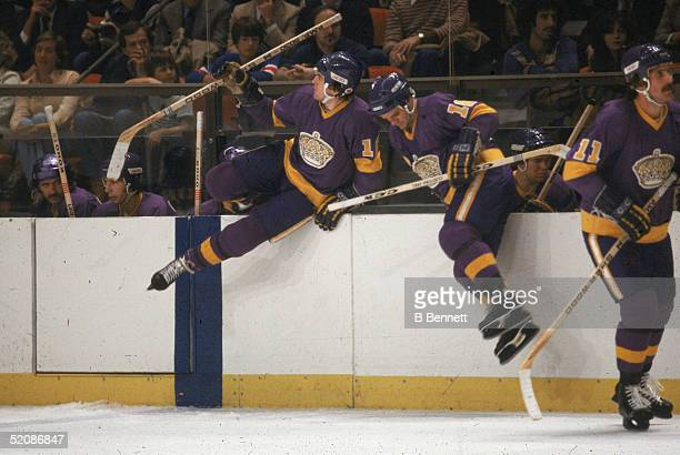 From left Canadian hockey players Dave Taylor Marcel Dionne and Charlie Simmer of the Los Angeles Kings jump onto the ice during a game against the...