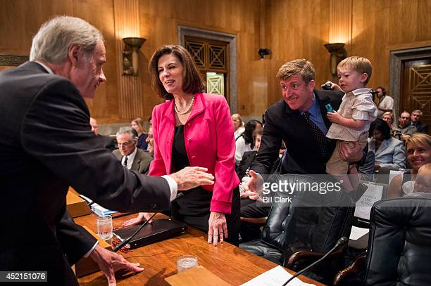 From left Chairman Tom Carper DDel greets Vicky Kennedy at the witness table as former Rep Patrick Kennedy DRI stands with his son Owen during the...