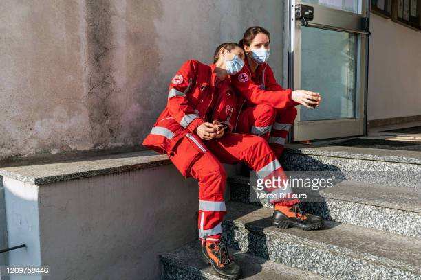 From left, crew members of an Italian Red Cross ambulance, Marilena Perruzzetto and Lisa Boni are sitting on the steps of the headquarters during...