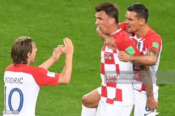 Croatia's midfielder Luka Modric Croatia's forward Mario Mandzukic and Croatia's defender Dejan Lovren celebrate an own goal by Nigeria's midfielder...