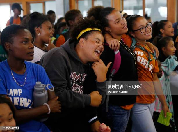 From left Damaris Sweeney of Milton watches the slideshow as her fellow group leader Paige Belfield of Boston sings along to the song playing and...