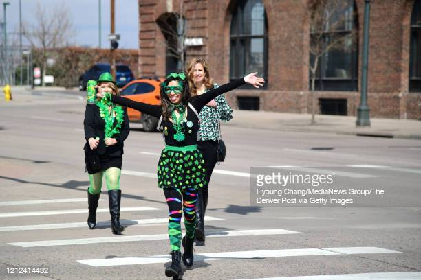 From left Denelle Gurule Vanessa Weingart and Micelle Brower are celebrating at the empty street of Lower Downtown in Denver Colorado on Saturday...