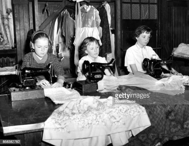 From left Diane McLaughlin Eileen O'Connor and Susan Bretagne work on sewing at a Boston Girls' Club on Apr 21 1961