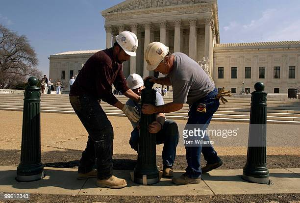 From left Edwin Medrano Rich Minnick and Lynn Funk of Walsh Construction install security bollards in front of the Supreme Court The bollards are...