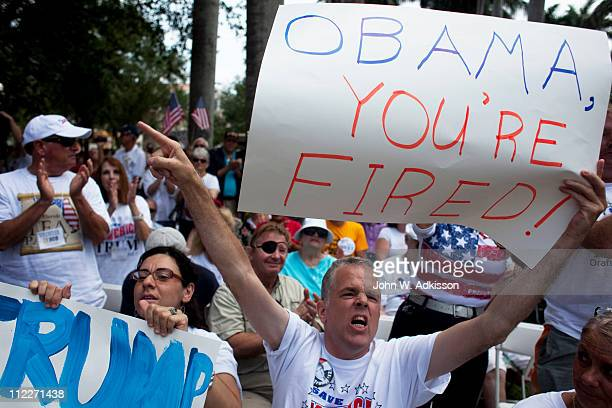 From left Fatima Berrahal and Educardo Burkhart of West Palm Beach listen to billionaire Donald Trump as he addresses a crowd at the 2011 Palm Beach...