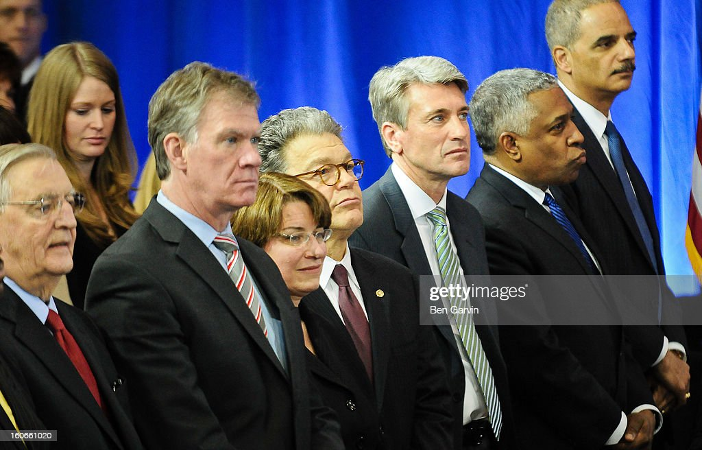 From left, former Vice President Walter Mondale, St. Paul Mayor Chris Coleman, U.S. Sen. Amy Klobuchar (D-MN), U.S. Sen. Al Franken (D-MN), Minneapolis Mayor R.T. Rybak, US Attorney for Minnesota B. Todd Jones and US Attorney General Eric Holder listen as President Barack Obama speaks before a crowd of local leaders and law enforcement officials at the Minneapolis Police Department Special Operations Center on February 4, 2013 in Minneapolis, Minnesota. President Obama is promoting a ban on assault weapons and expanded background checks on gun buyers.