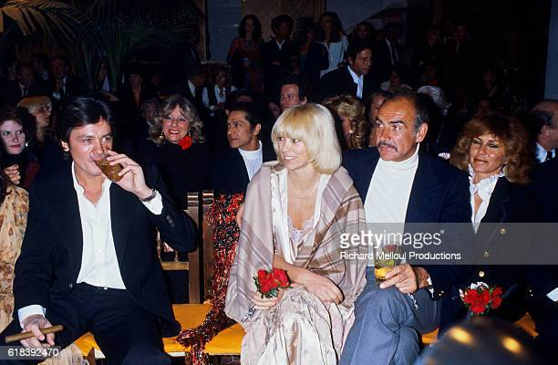 From left French actor Alain Delon actress Mireille Darc and Scottish actor Sean Connery enjoying the entertainment at the inauguration of Regine's...