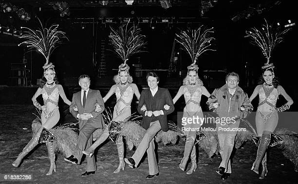 From left French television talk show hosts Philippe Bouvard Michel Drucker and Jacques Martin dancing arm in arm with the Bluebell Girls The famed...