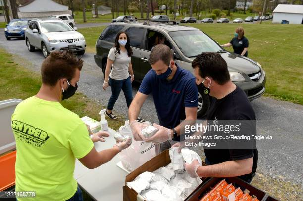 From left front are Mark Snyder Jr Kevin Snyder and Mark Snyder assembling meals for people in cars as Lyndy Embriani back left waits to take the...