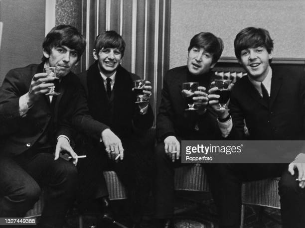 From left, George Harrison, Ringo Starr, John Lennon and Paul McCartney of English pop group The Beatles raise their glasses for a toast backstage at...