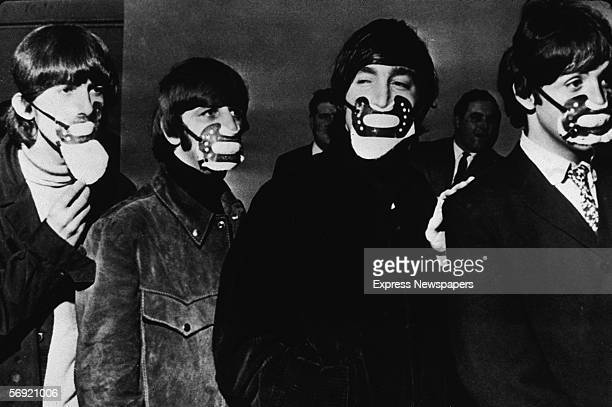 From left George Harrison Ringo Starr John Lennon and Paul McCartney of the British pop group the Beatles walk in single file all wearing fog masks...
